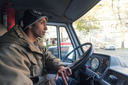 dumps: ZAGREB, CROATIA - OCTOBER 17, 2013: Young Roma man driving a van in search for street garbage dumps. Editorial