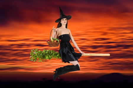 Young woman dressed as a witch carrying vegetable basket and riding a broom. Orange sunset in background. photo