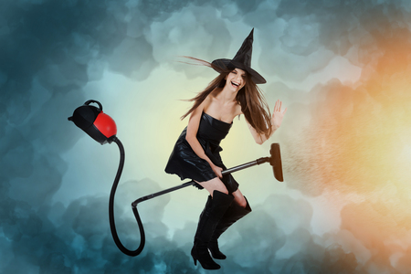 Young woman dressed as a witch riding a vacuum cleaner. Cleaning concept. photo