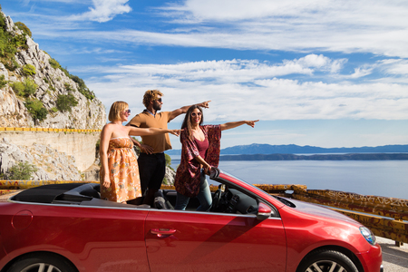Group of happy young people waving and pointing fingers from the red convertible. Stock Photo