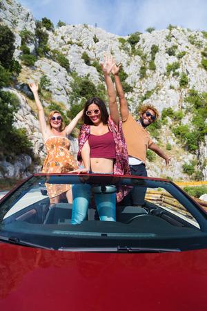 personas saludando: Grupo de gente joven feliz saludando desde el convertible rojo. Foto de archivo