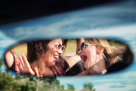 Two happy girls in a car rear-view mirror.