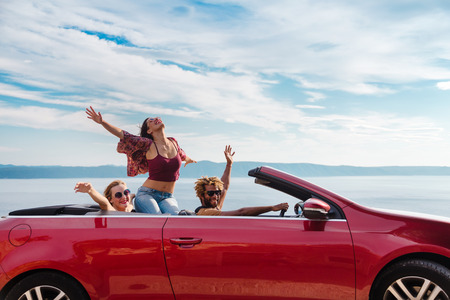 Group of happy young people waving from the red convertible. Stock Photo