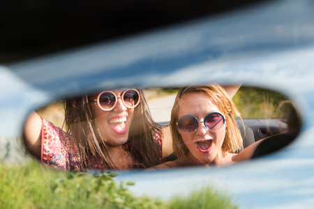 rearview: Two happy girls in a car rear-view mirror.