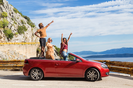 Group of happy young people standing in the red convertible car and waving. Stock Photo