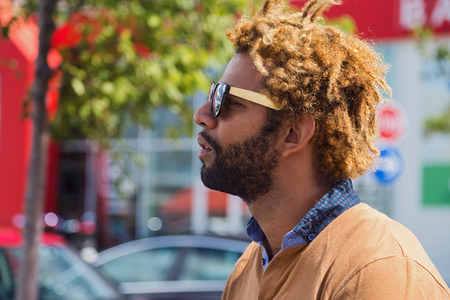 good weather: Portrait of young black man with dread locks wearing sunglasses.