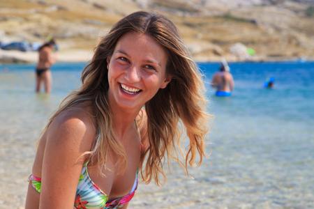 joyfull: Beautiful tanned girl in a bikini sitting on a rocky beach.