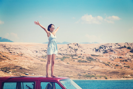 travel woman: Beautiful tanned girl in a blue dress standing on a rooftop of red van and spreading arms. Post processed with vintage filter. Stock Photo