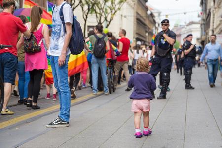 ZAGREB, CROATIA - JUNE 11, 2016: 15th Zagreb pride. Little kid on the street next to LGBTIQ activists.