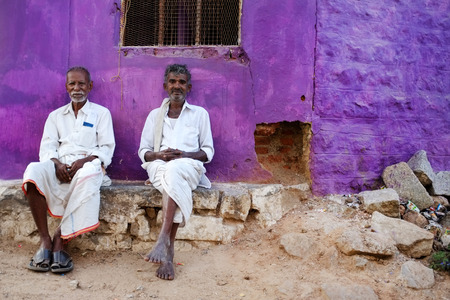 KAMALAPURAM, INDIA - 02 FEBRUARY 2015: Local Indian men resting and socialising on the street in front of a purple coloured home. Editorial