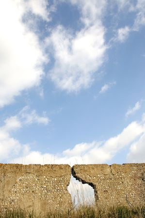 flint: a old flint wall with a large crack in it. With blue sky