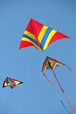 Three kites flying in a blue sky Stock Photo