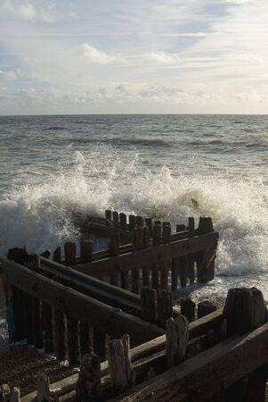 groyne: Waves Crashing Over Wooden Groyne Stock Photo