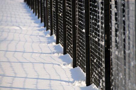 Black metal fence in the snow Stock Photo - 6186525