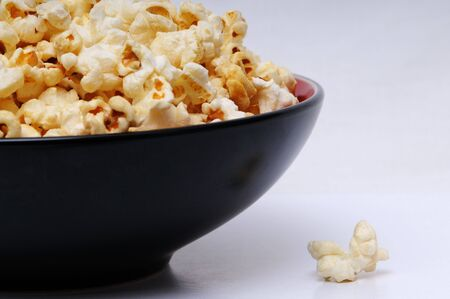 A shot of a bowl of popcorn on a white background. Stock Photo