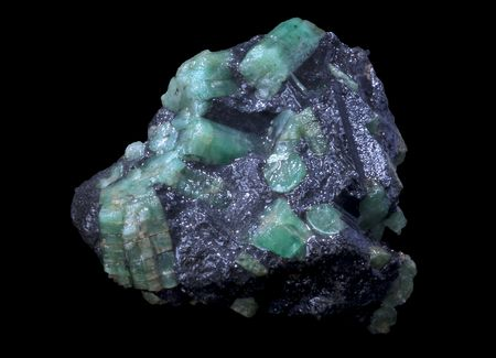 materia prima: piedra verde esmeralda en un fondo negro aislado