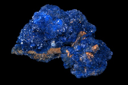 gem: Azurite is a soft, deep blue copper mineral produced by weathering of copper ore deposits. Isolated in black background.