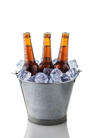 vasos de cerveza: botellas de cerveza en un cubo de hielo aislados sobre fondo blanco Foto de archivo