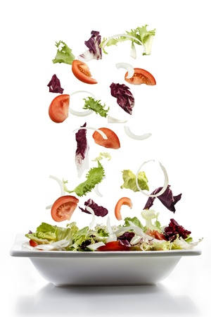 salad with fresh vegetables falling on plate, mediterranean cuisine photo