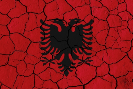 Flag of Albania over cracked background, conceptual image of crisis photo