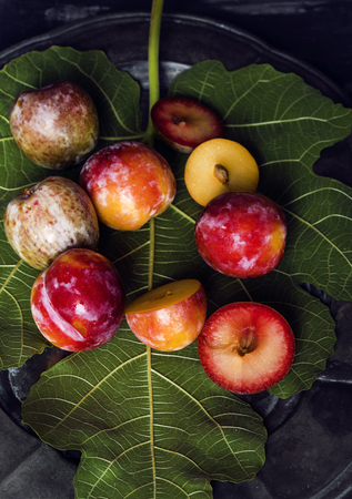 Plums pieces in dark table with green leaf