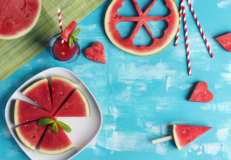 Watermelon slices and hearts in blue wooden background