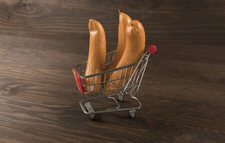 Sausages in supermarket cart with wooden backgroud