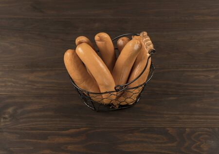 Close-up sausages with metal basket on wooden background. View from above 版權商用圖片