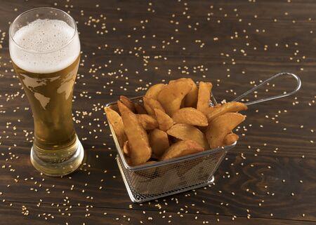 Patatoe wedges in metal basket with beer