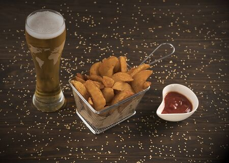 Beer with patatoes wedges and ketchup