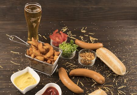 Sausages with various condiments on wooden bord with cold beer