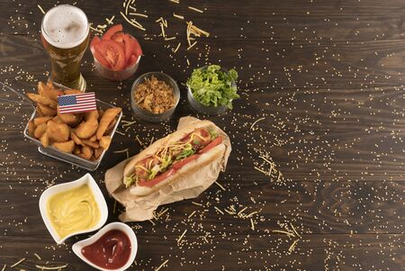 Hot dog with condiments, sauces and potatos wedges.View aboved.american flag Banco de Imagens