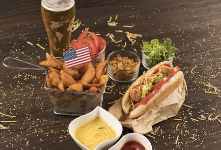Hot dog with condiments and patatos wedges.american flag