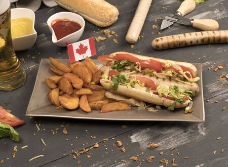 Homemade hot dog with white sausages with various condiments front view on gray wooden board and Canada flag
