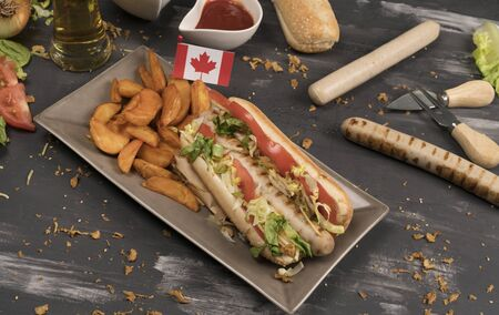 Homemade hot dog with white sausages with various condiments and Canadian flag viewed from above on gray wooden board