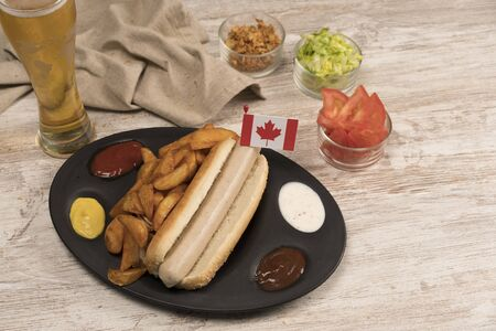 Homemade hot dog with white sausages on tray with various condiments and Canadian flag viewed from above Banco de Imagens