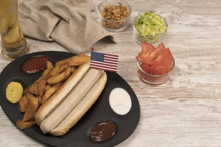 Homemade hot dog with white sausages on tray with various condiments and American flag viewed from above
