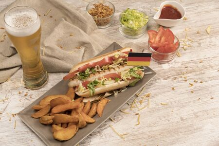 Hot dog with white sausage various seasonings on white wooden board top view with German flag