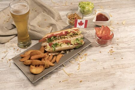 Homemade hot dog on white wooden board with various condiments top view with Canada flag