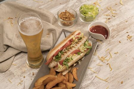 Hot dog with homemade white sausage on white wooden board top view Banco de Imagens