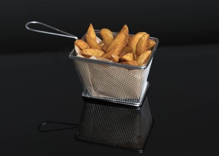 fried potato wedges on black methacrylate in metal basket top view