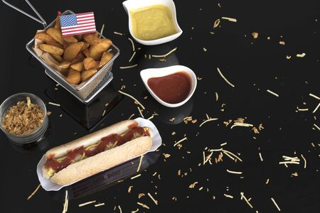 Hot dog with condiments, sauces and potato wedges seen from above with usa flag
