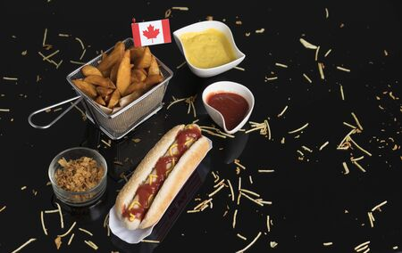 Hot dog with condiments, sauces and potato wedges in black methacrylate with Canadian flag