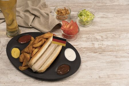 Hot dog with various condiments, sauces and wedges of potato and beer with German flag