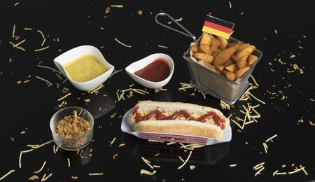 Hot dog with condiments, sauces and potato wedges in black methacrylate front view