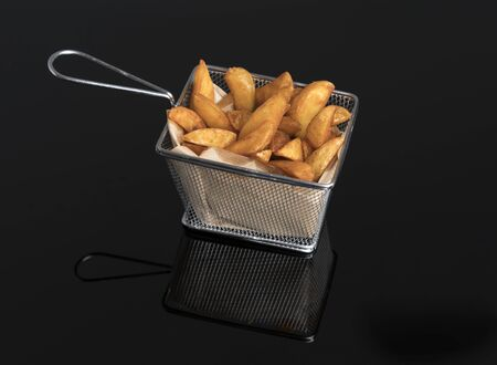 Fried potato wedges on black methacrylate in metal basket