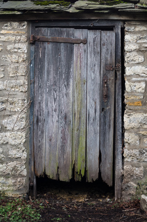 view of a wooden doorway: Old rotten door in a village graveyard