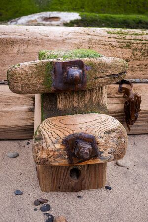The waves sweep out and etch their movements on the resilient groynes which stand on the beach at Sandsend