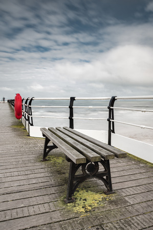 Empty bench on Saltburn Pier, early spring day. Saltburn by the sea, North Yorkshire. UK.