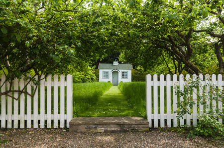 A childs white playhouse at the end of a grass path, white picket fence entrance.